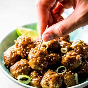 female hand sticking toothpick into meatball