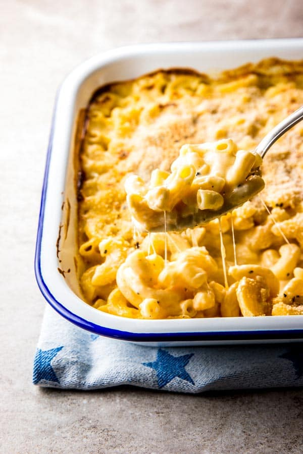 Scooping creamy homemade baked mac and cheese out of the casserole dish. It looks so cheesy!