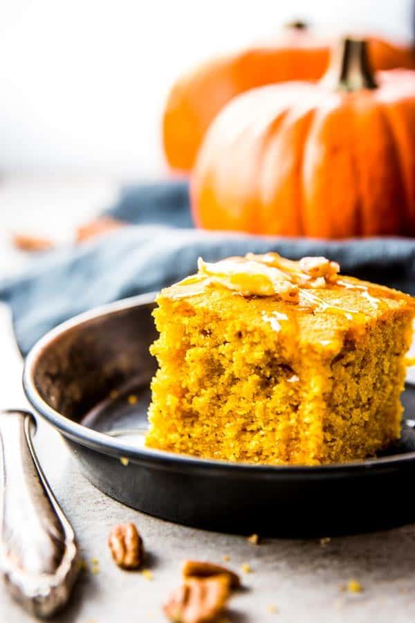 slice of pumpkin cornbread on metal dish in front of pumpkin