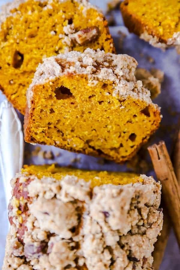slices of streusel pumpkin bread stacked on a board