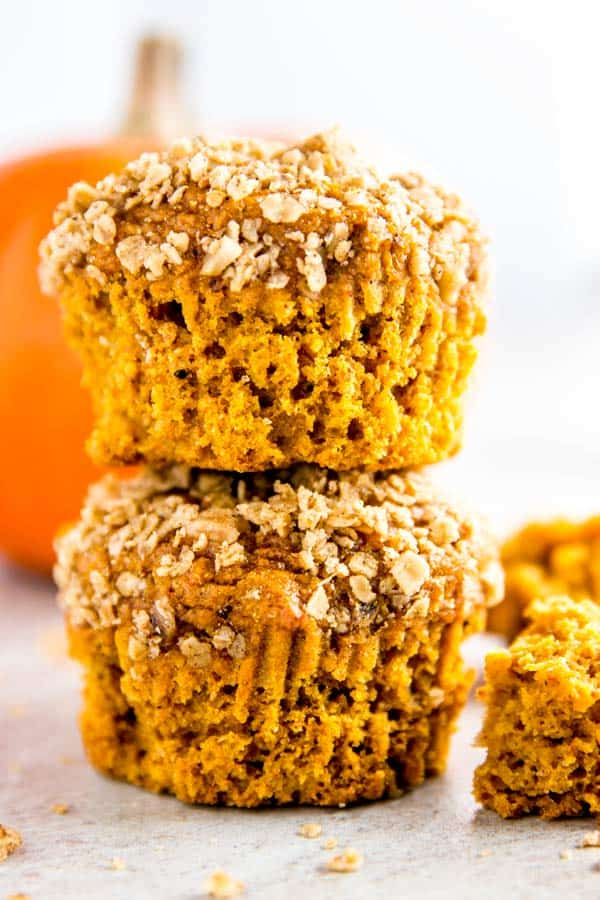 stack of healthy pumpkin muffins with a small orange pumpkin in the background