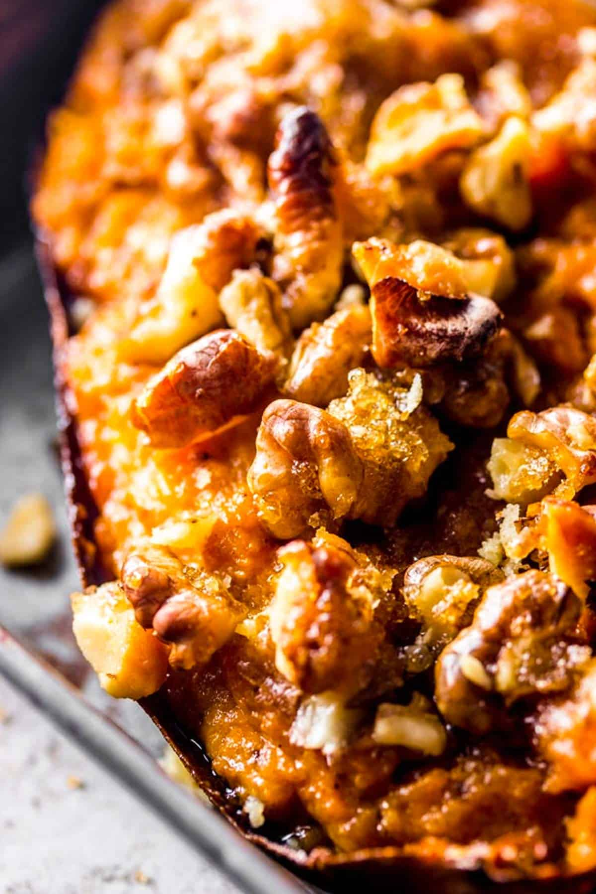 extreme close up of maple walnut topping on a twice baked sweet potato skin