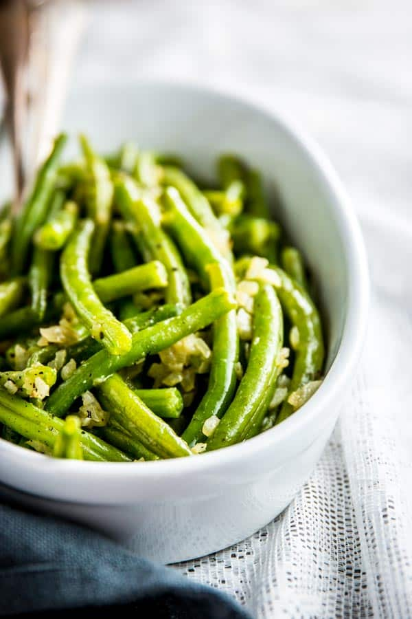 green beans with diced onion in white dish