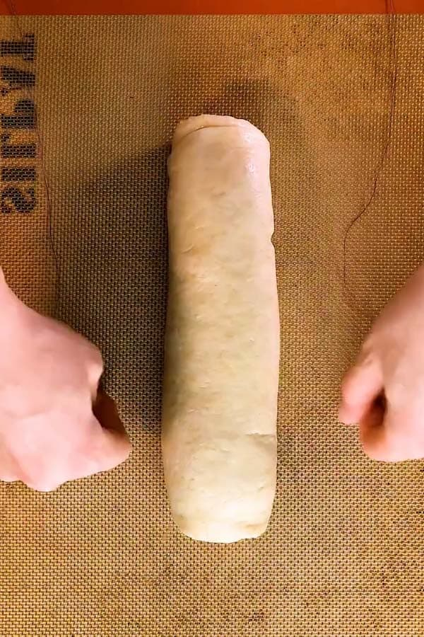 cutting a log of dough into cinnamon rolls with a pice of string - 1