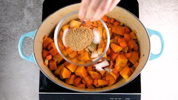 Adding brown sugar to pumpkin soup.