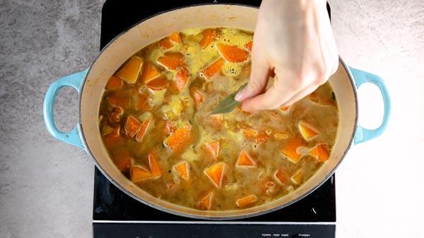 Adding a bay leaf to simmering pumpkin soup.