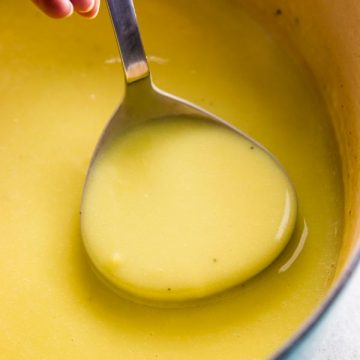 close up photo of ladle with potato leek soup in Dutch oven