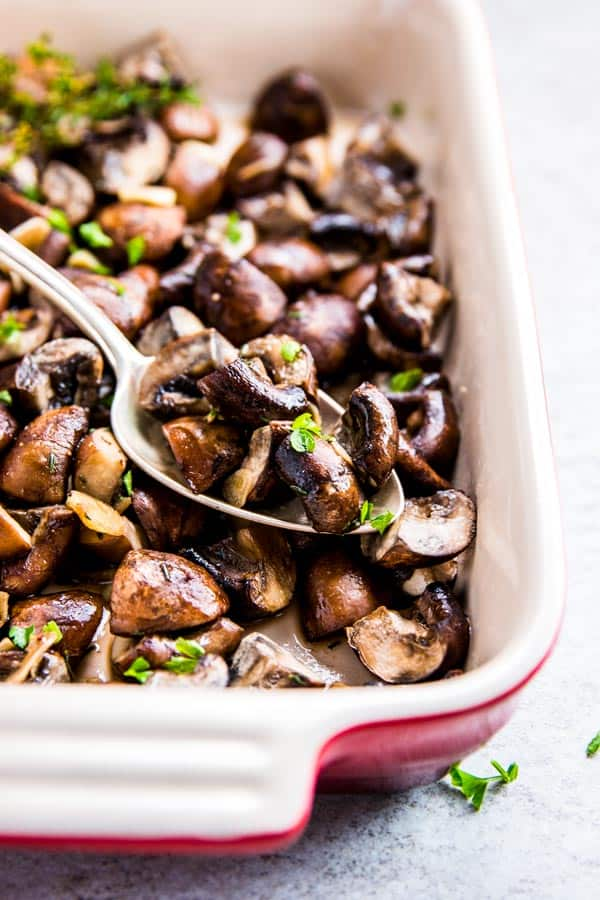 Garlic Butter Mushrooms in a casserole dish with a spoon.