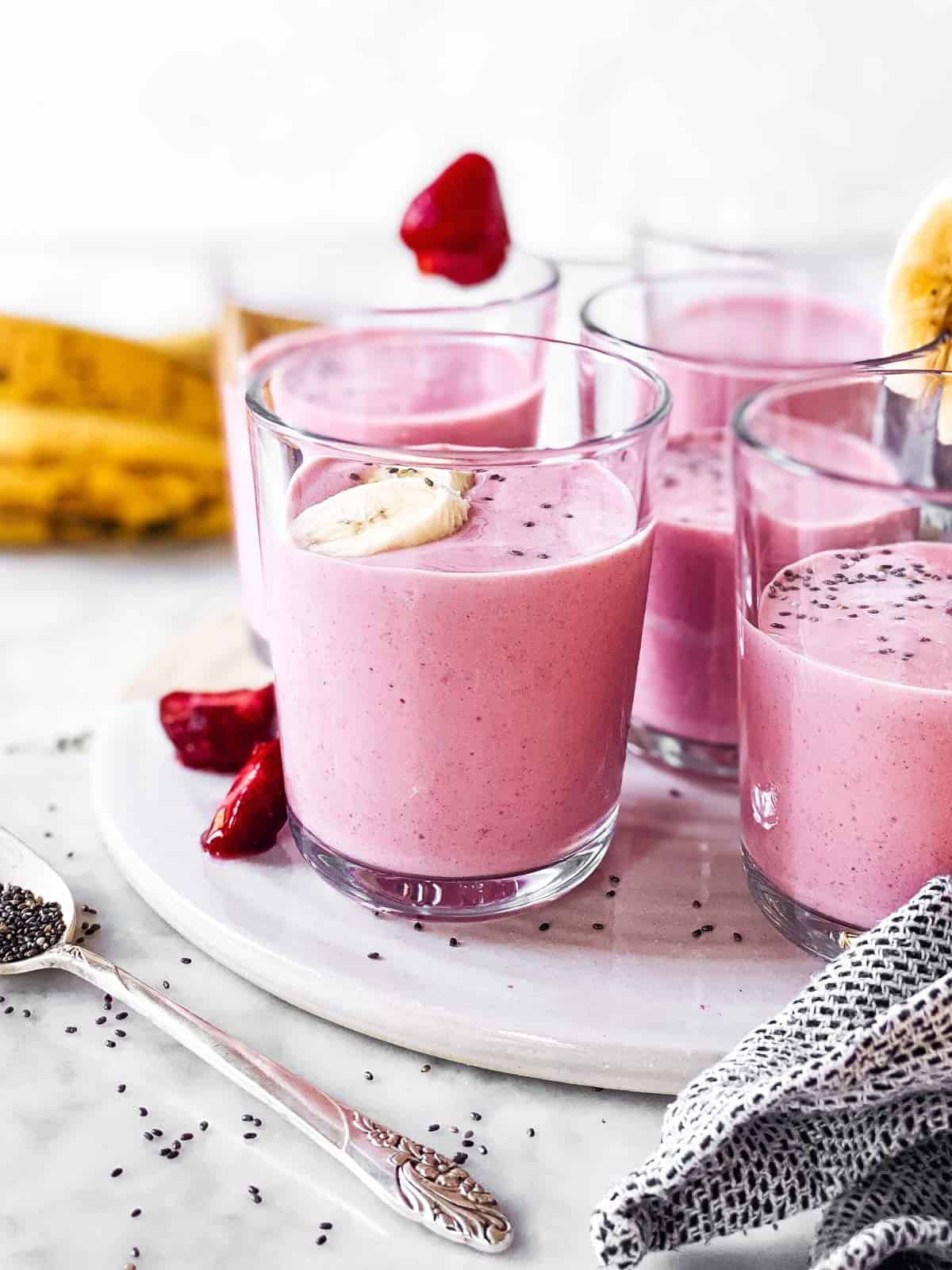 several glasses with strawberry banana smoothie on white platter
