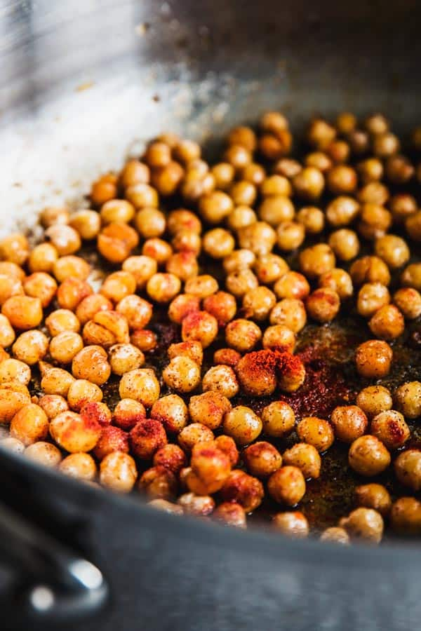 Chickpeas in a skillet with olive oil and smoked paprika.