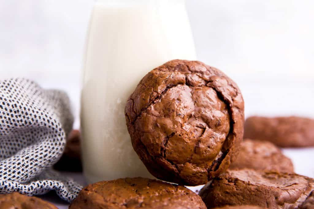 brownie cookie leaning against a bottle of milk