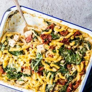 Chicken Florentine Pasta Casserole in a enamel casserole dish with a silver spoon.