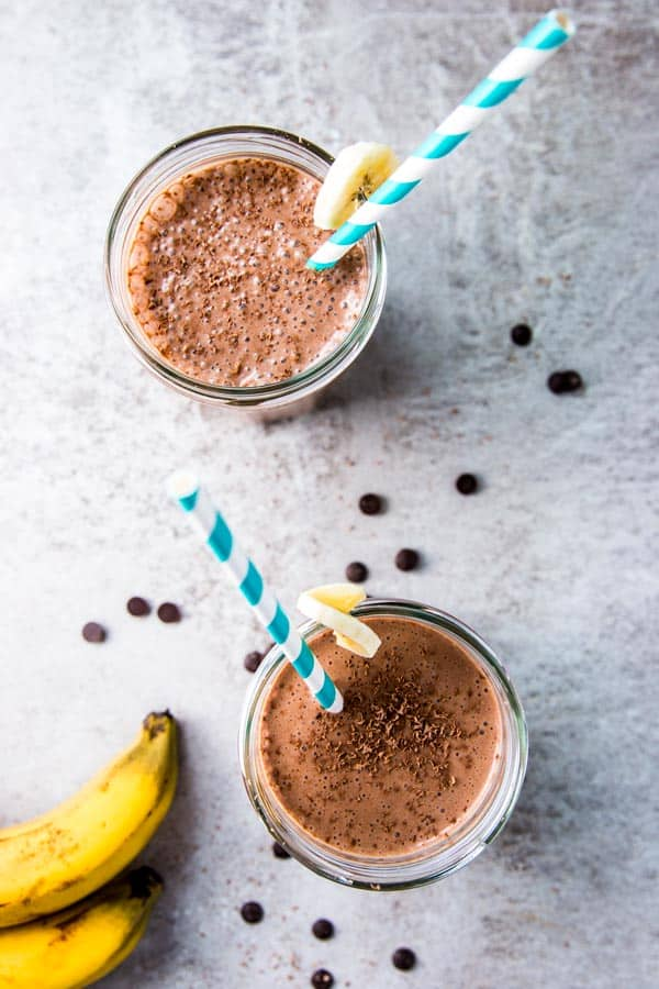 Two glasses of chocolate peanut butter banana smoothie, with bananas and chocolate chips