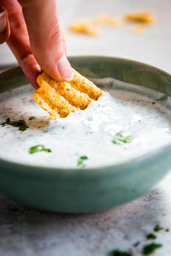 Dipping a chip in ranch dip.
