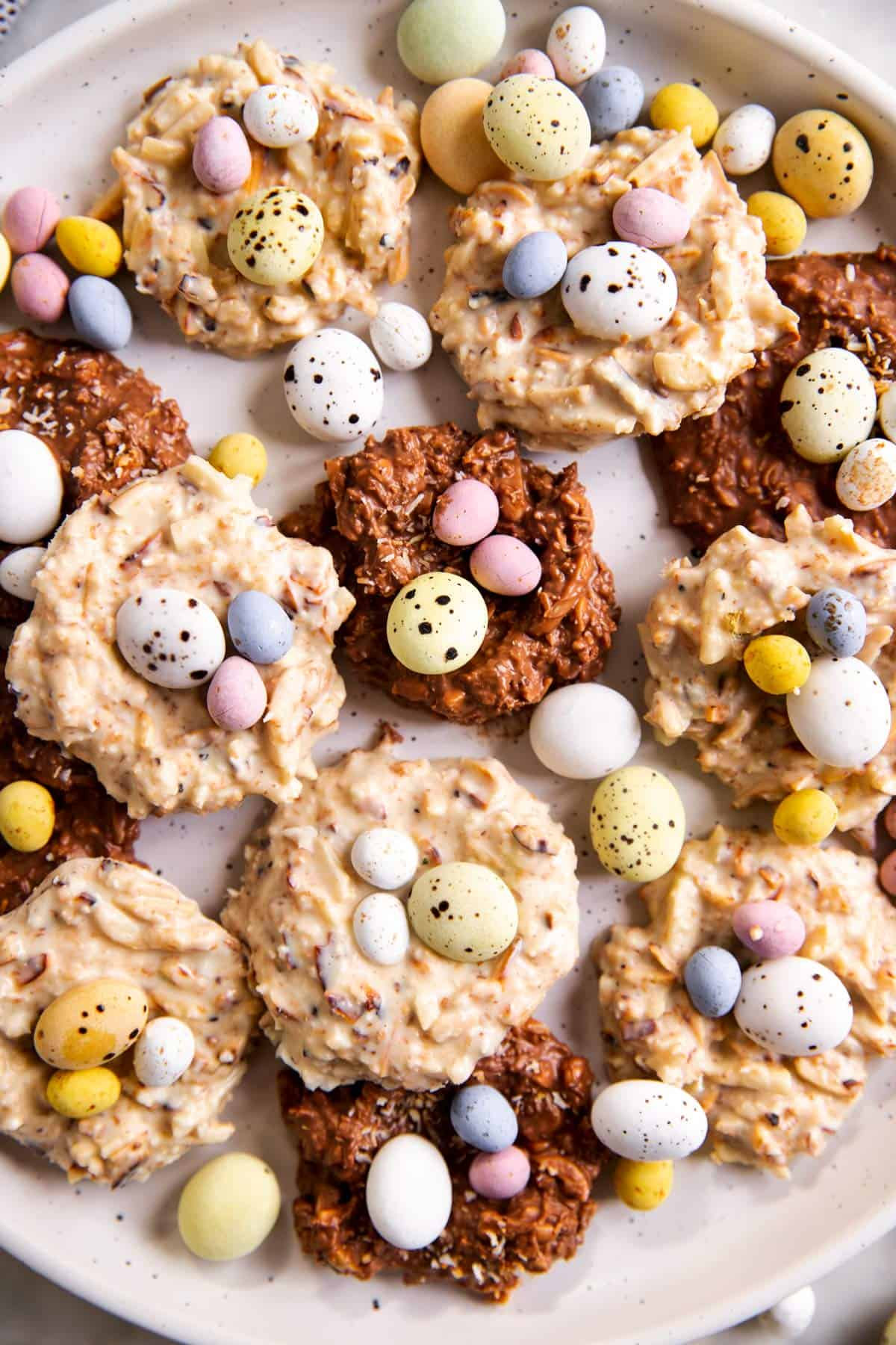 close up photo of several bird's nest cookies and scattered mini eggs on white plate