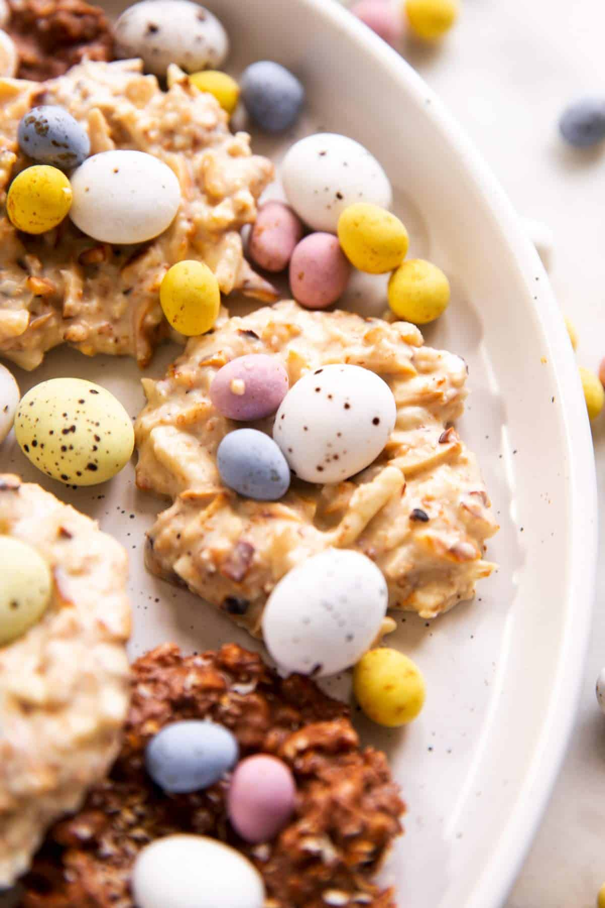 close up photo of white chocolate Bird's nest cookie on plate with several mini eggs and more cookies in background