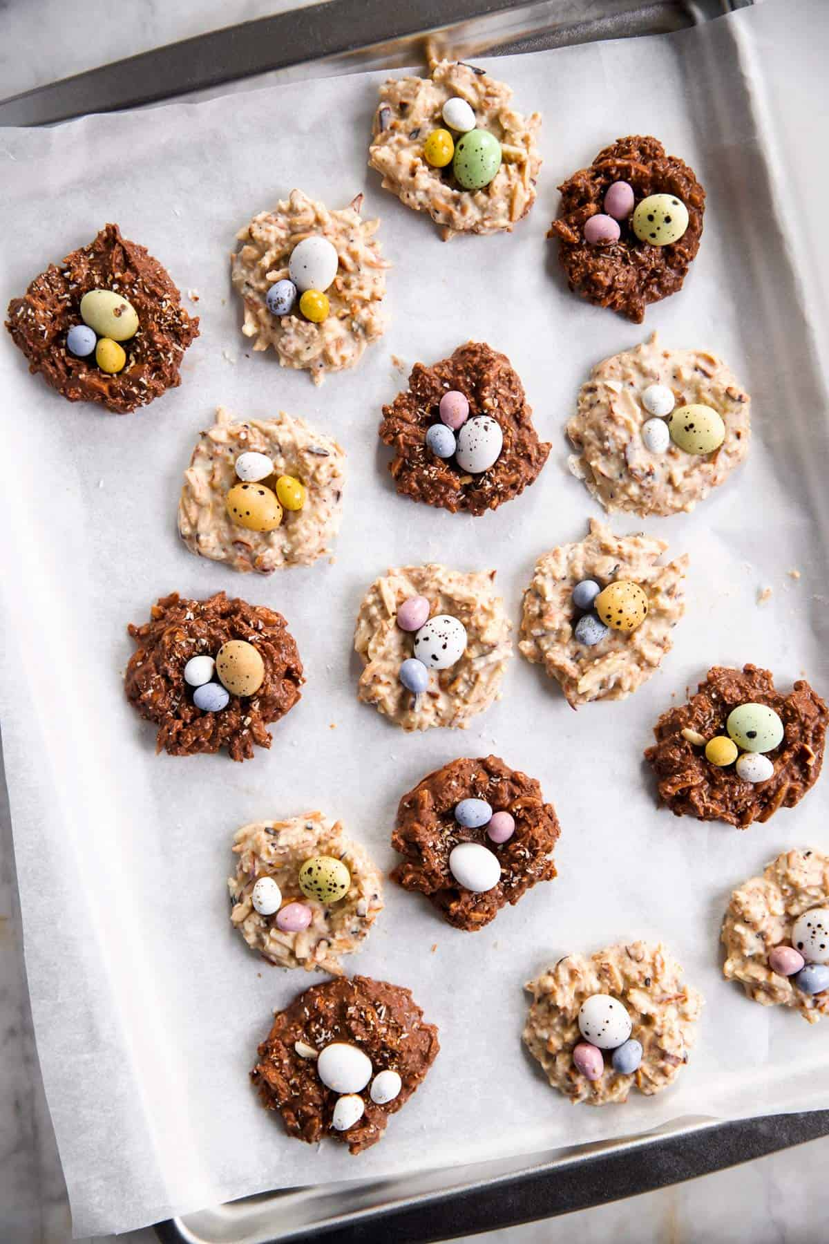 white and brown bird's nest cookies scattered over rimmed sheet pan lined with white baking parchment