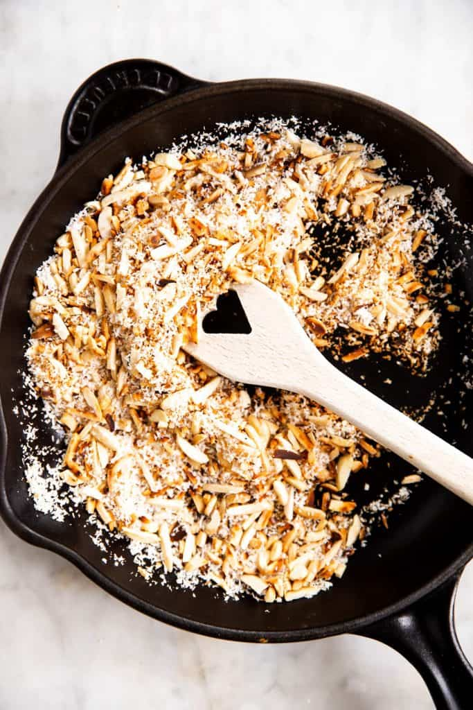 toasted almonds and shredded coconut in black cast iron skillet