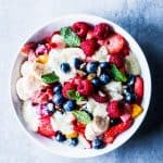 Creamy fruit salad in a white bowl on a light blue surface.