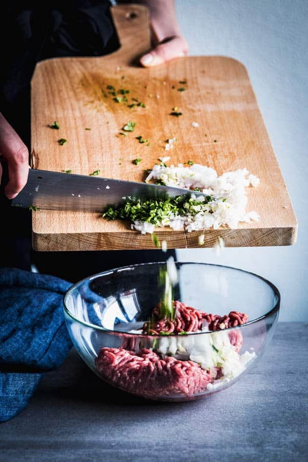 Woman pushing chopped cilantro, onion and garlic off a wooden chopping board into a glass bowl with ground beef.