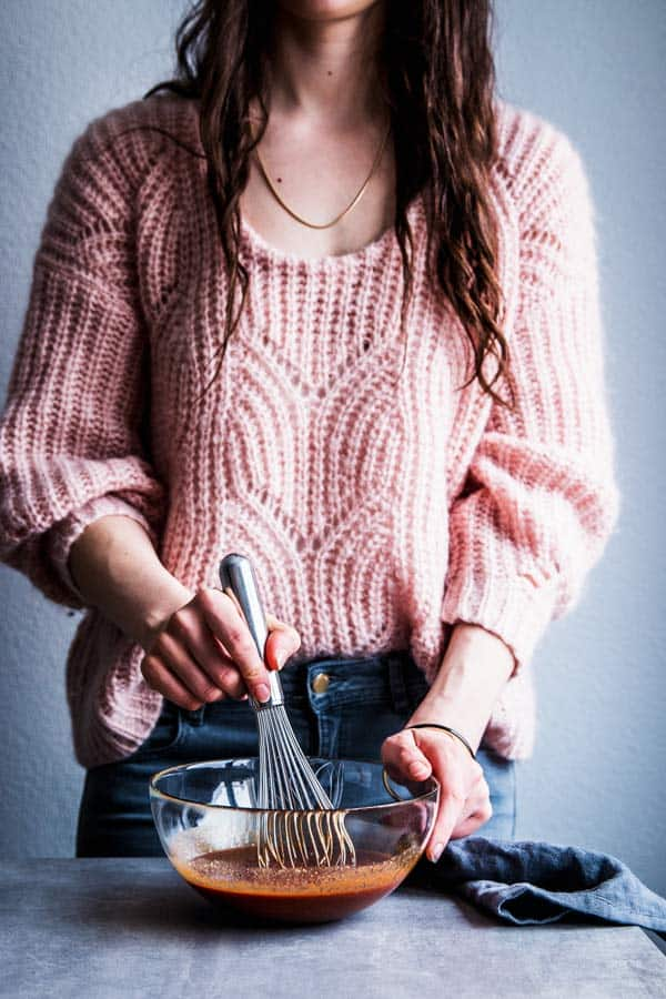 Woman in a pink sweater whisking pineapple bbq sauce.