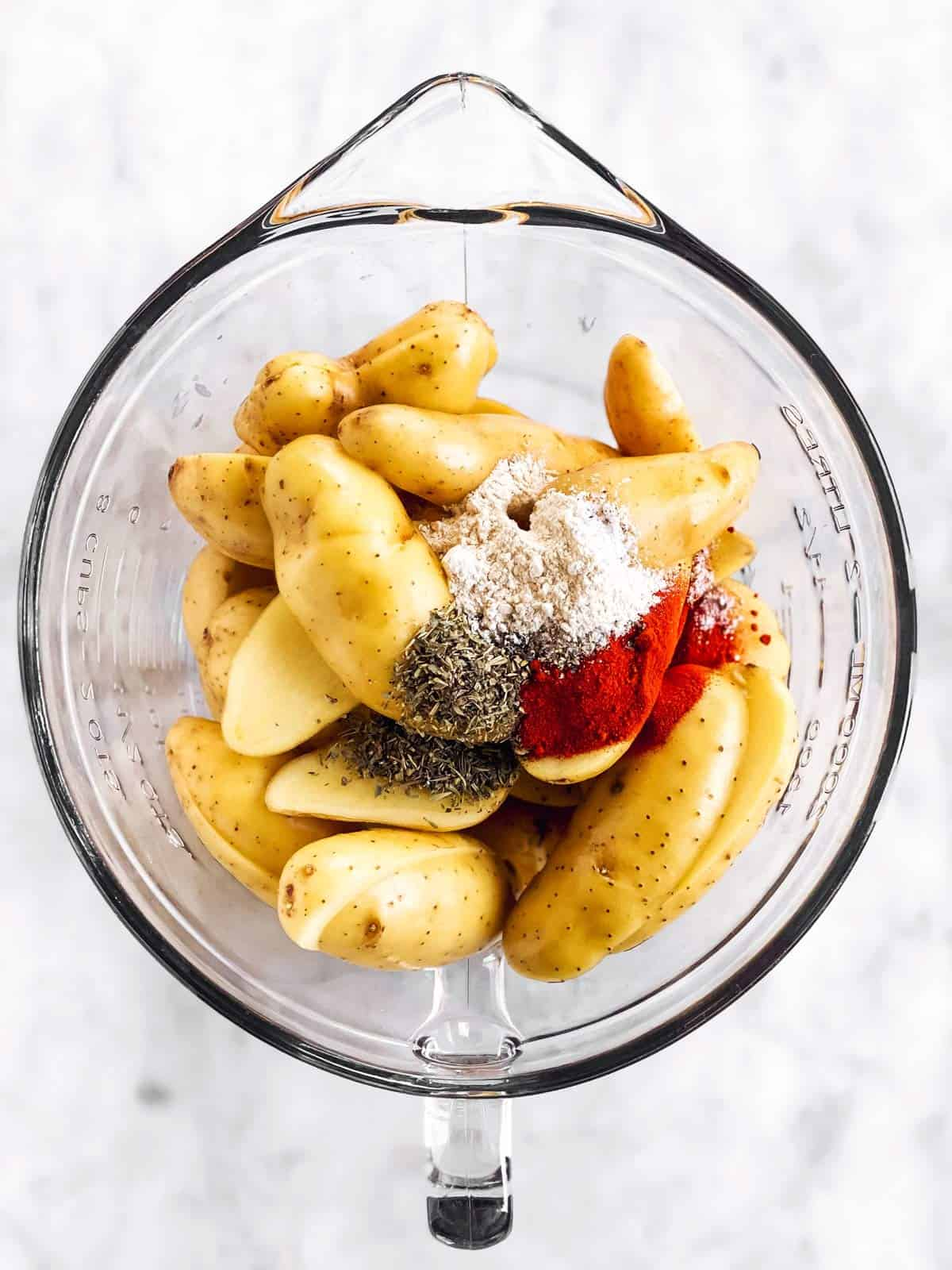 glass bowl filled with halved fingerling potatoes and seasoning