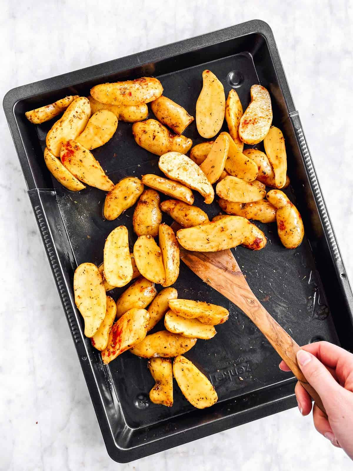 female hand tossing potatoes with wooden spoon on dark pan