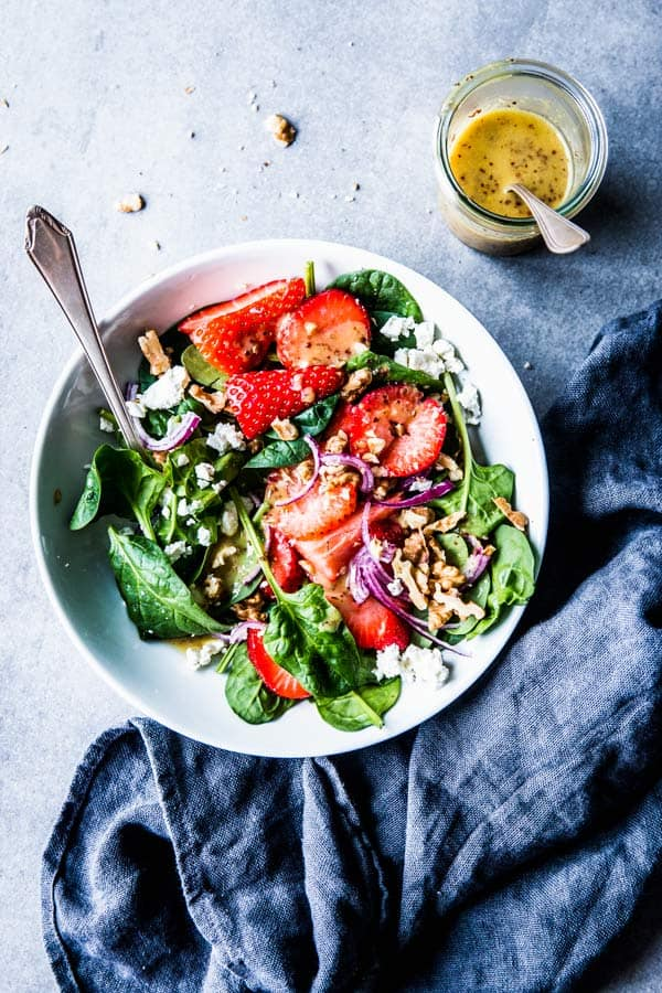 Spinach Strawberry Walnut Salads in a white bowl with a black napkin and a jar of dressing.