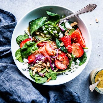 Spinach Strawberry Walnut Salad in a white bowl with dressing on the side.