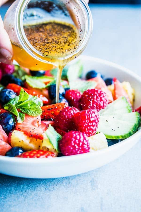Pouring poppy seed fruit salad dressing over summer fruit salad.