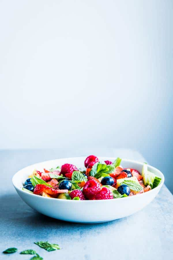 Summer Fruit Salad in a white bowl on a table.