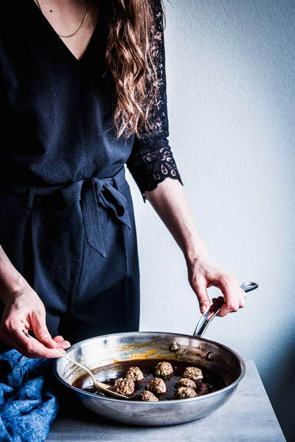 Woman in a black jumpsuit, adding meatballs to teriyaki sauce.
