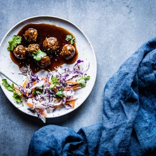 Teriyaki meatballs on a white plate with coleslaw, a fork and a dark napkin.