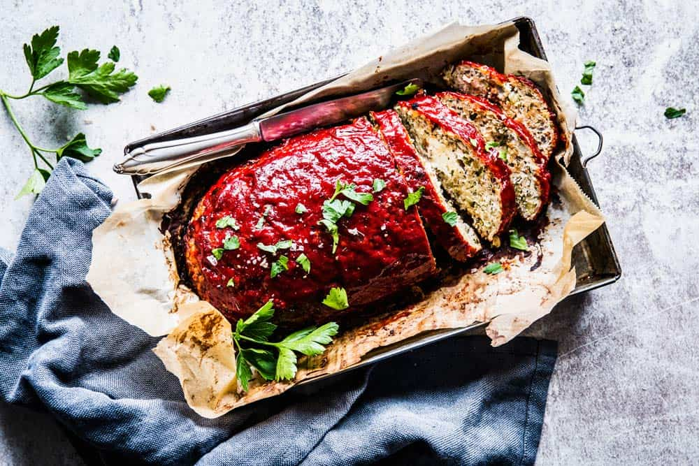 Turkey Zucchini Meatloaf on a sheet pan with a dark napkin.