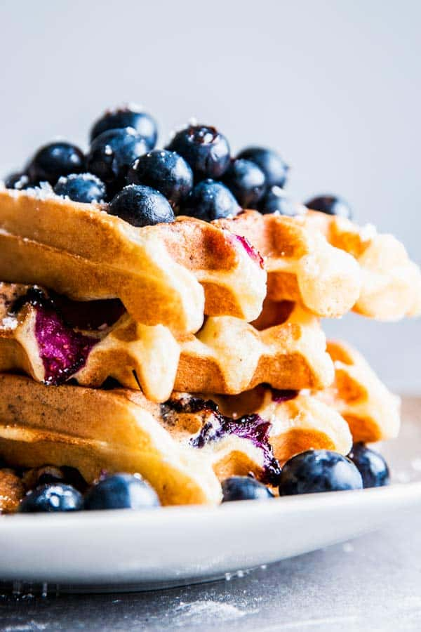 Stack of blueberry waffles on a plate.