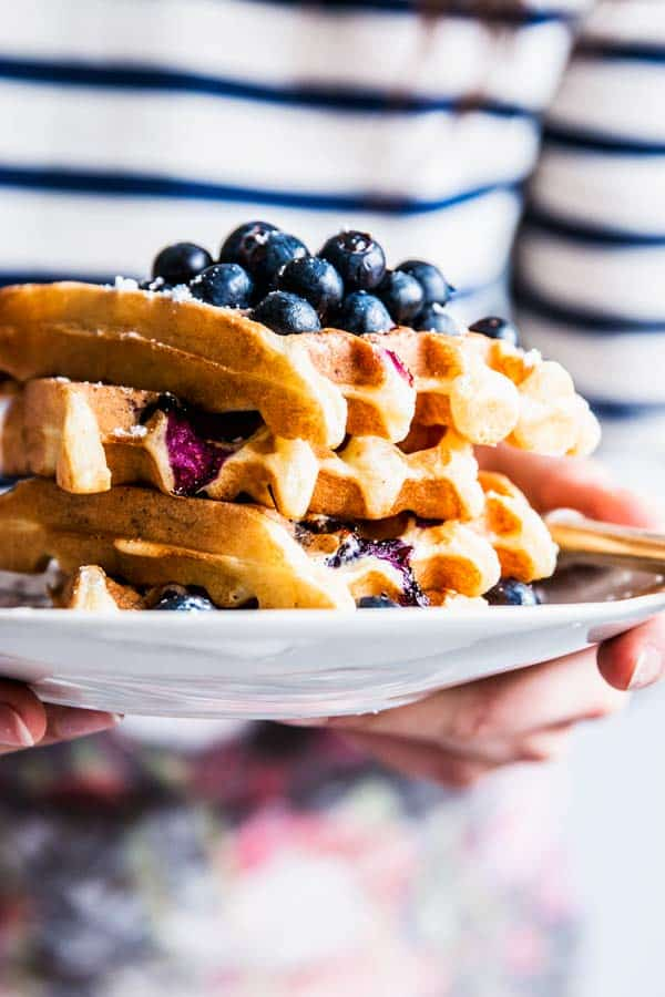 Woman in a striped shirt holding a plate with a stack of blueberry waffles.