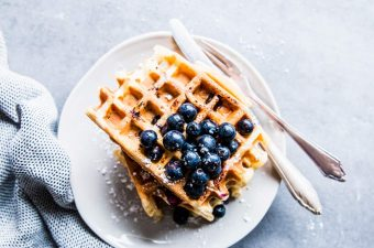 Blueberry waffles on a white plate with cutlery.