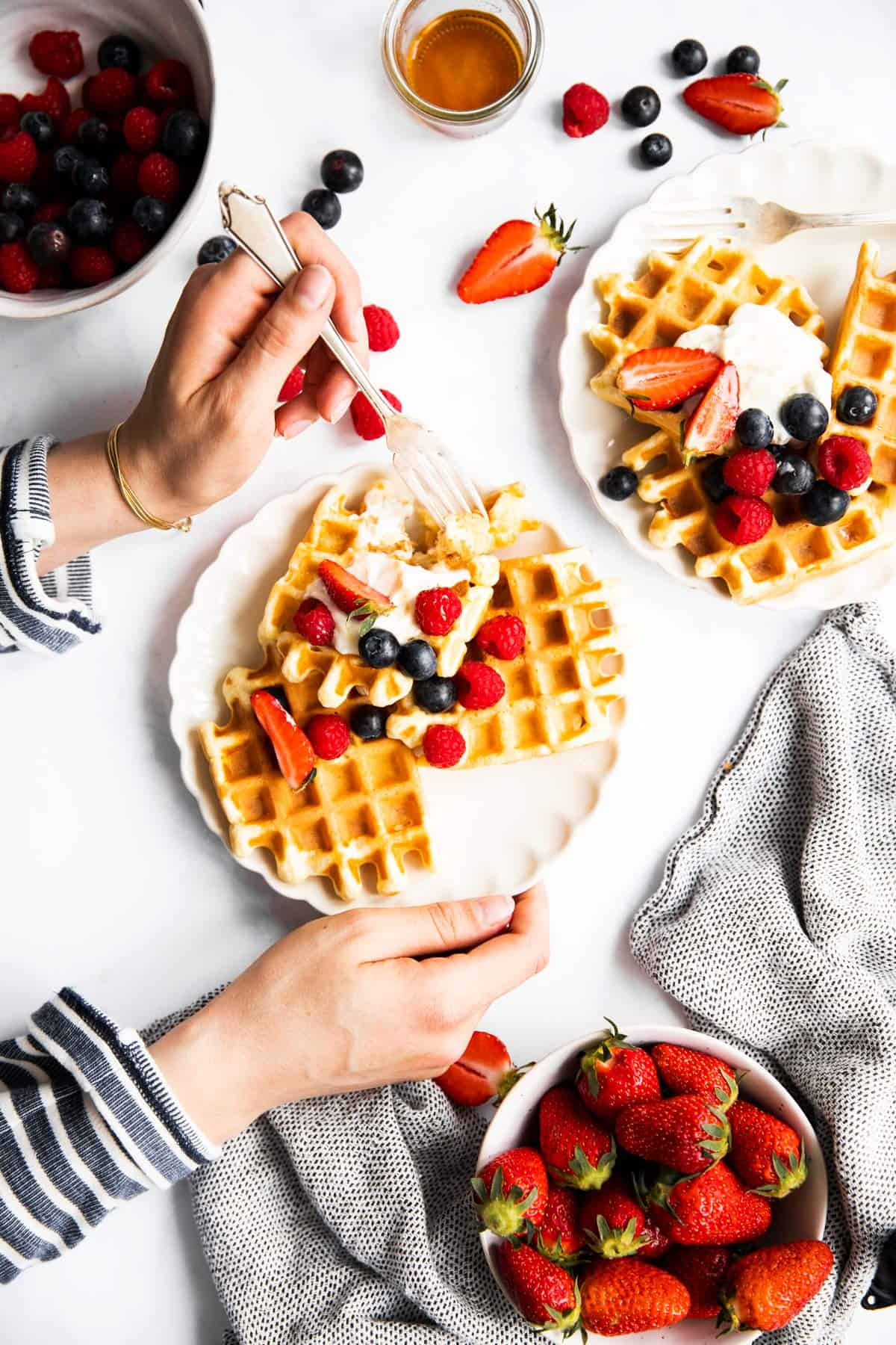 female hands holding plate with waffles and berries
