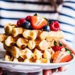 Woman in a striped shirt holding a plate with a stack of buttermilk waffles.