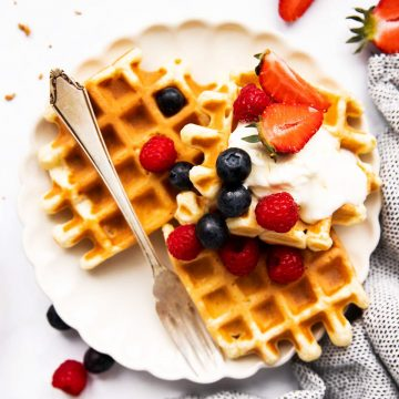 top down view on plate of buttermilk waffles garnished with berries and cream