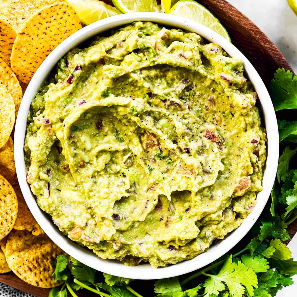 overhead view of bowl with guacamole on platter with corn chips
