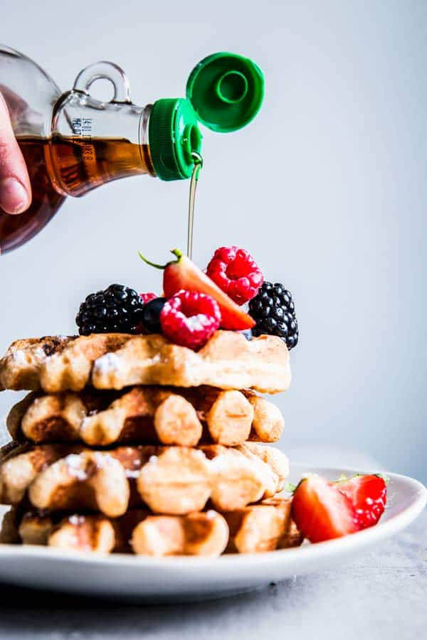Pouring maple syrup over a stack of Fluffy Whole Wheat Waffles with berries.