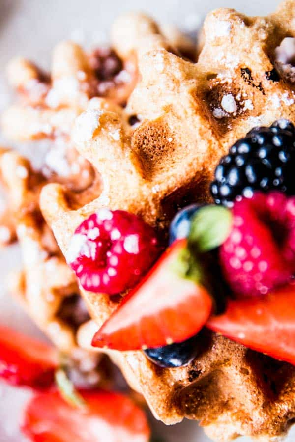 Close up photo of Fluffy Whole Wheat Waffles topped with berries.
