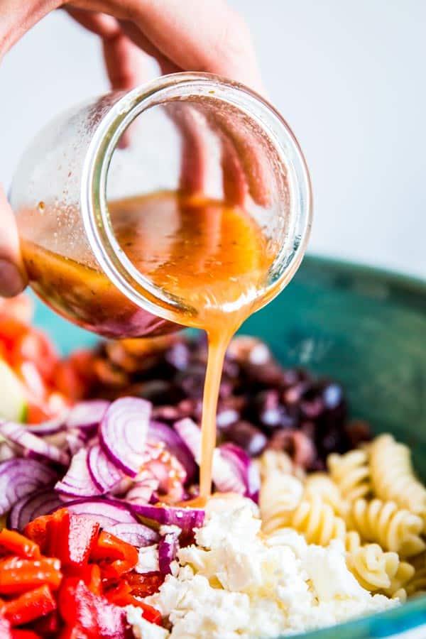 pouring greek salad dressing over greek pasta salad