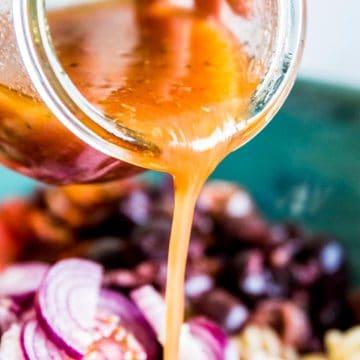 Pouring Greek Salad Dressing over salad