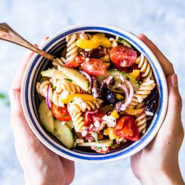 Holding greek pasta salad in a bowl