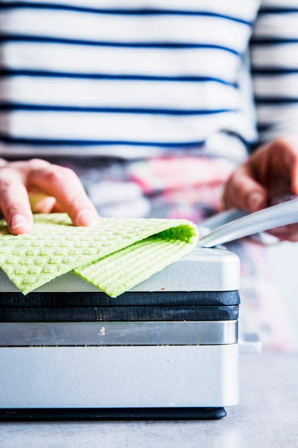 Wiping down a waffle maker with a green cloth.