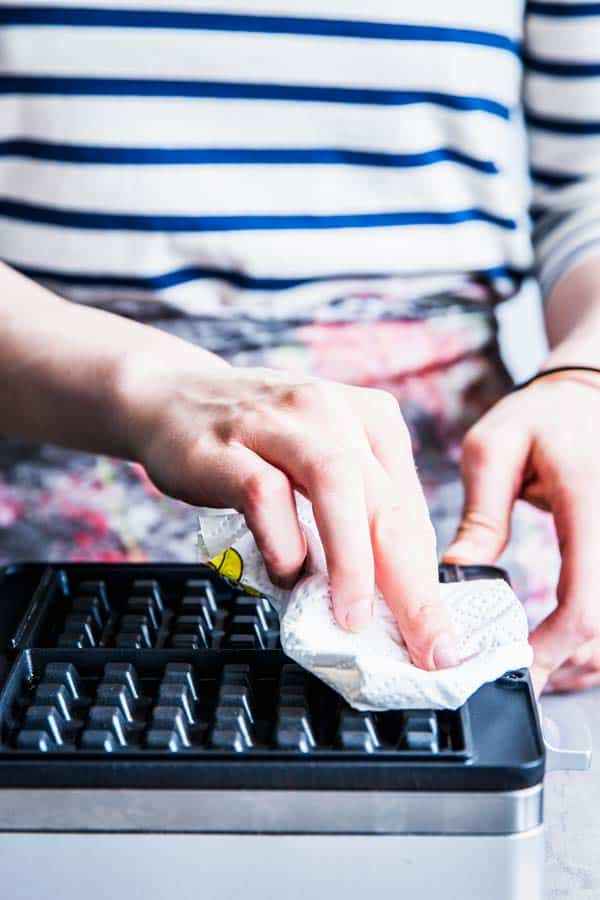 Woman in a striped shirt wiping down a waffle maker with a paper towel.
