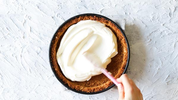 spreading cheesecake filling in a graham cracker crust for no bake strawberry pie
