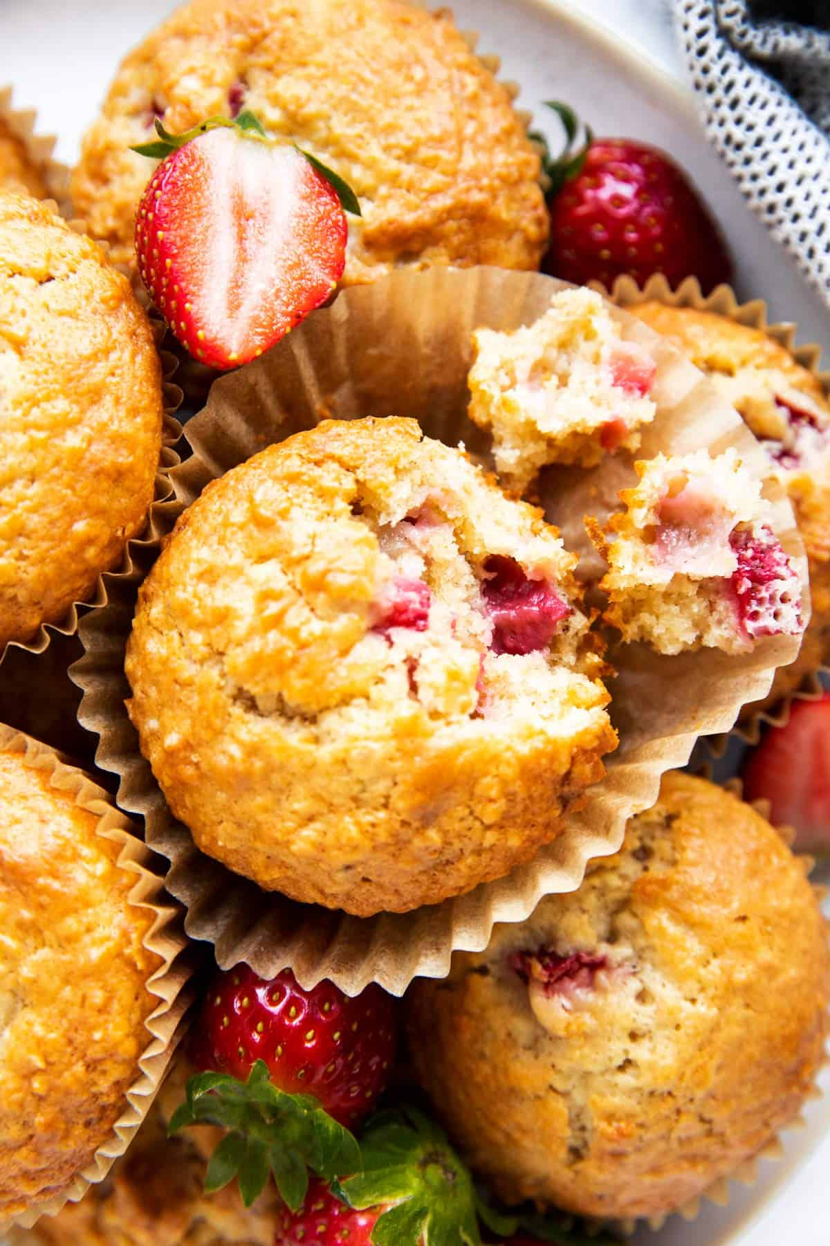 close up photo of a pile of strawberry muffins, one broken apart